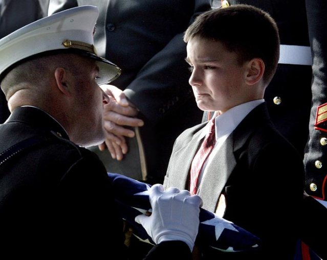 """""""Choking back tears, Christian Golczynski accepted the flag from his father's casket. Photographer Aaron Thompson described this moment as 'the most emotionally moving event I may have ever witnessed and may ever witness in my life'."""" From ABC News"""